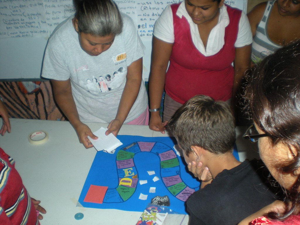 A group in Nicaragua field tests an educational board game. Courtesy Hesperian Health Guides.