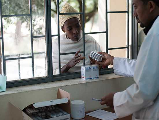 A SIAPS supported pharmacist hands medicine to a woman in Ethiopia.