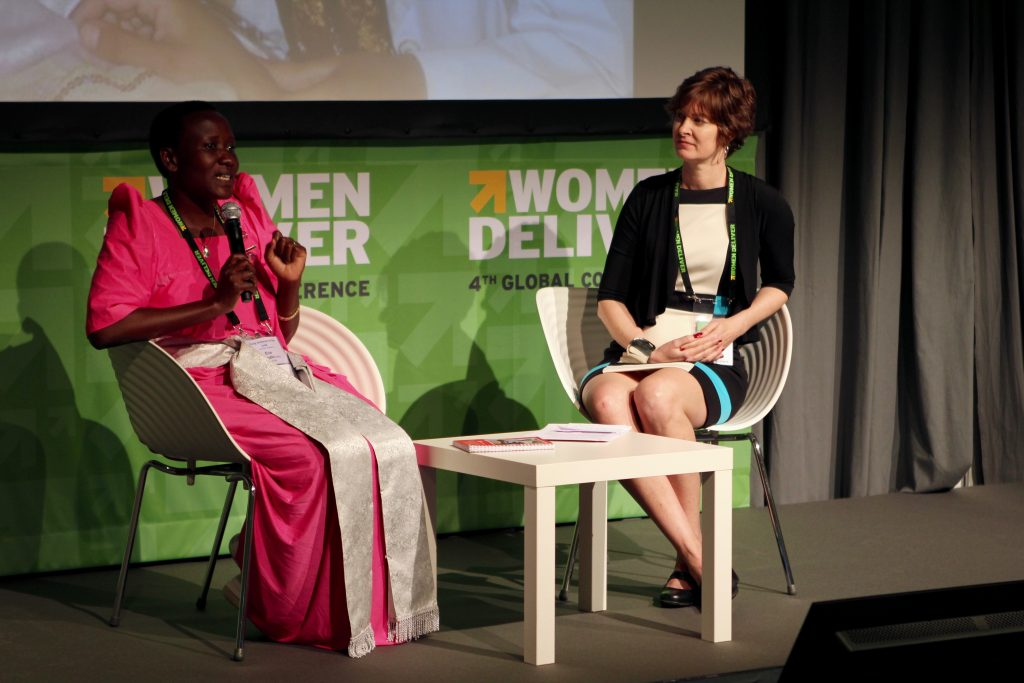 Eva Nangalo, a midwife from Nakaseke Hospital in central Uganda (left), speaks to Frontline Health Workers Coalition Chair Julia Bluestone of Jhpiego (right) at FHWC's Women Deliver side session focused on frontline health workers' stories. Courtesy Cole Bingham, Jhpiego.